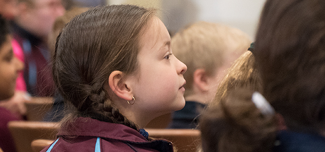 A picture of a student looking up and paying attention to our Pastor leading Chapel