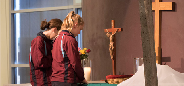 A picture of two senior students stand at the Chapel altar and bow their heads in prayer