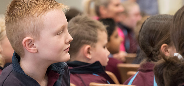 A year two boy leans in to watch Pastor present his message in Chapel