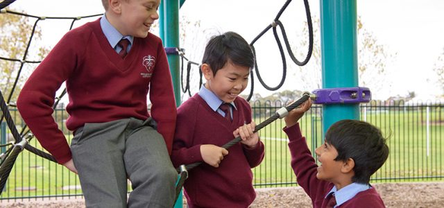 A picture of three year four boys happily chat among themselves on the playground