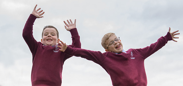A picture of two year two boys jumping up in excitement on the play equipment